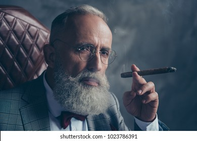 Close up portrait of harsh, brutal, old shareholder in glasses, holding cigar, looking at camera with serious expression, sitting on chair over gray backgrou