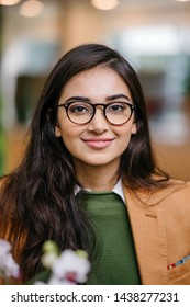 Close up portrait head shot of a beautiful, young and intelligent looking  business school MBA student in a preppy green sweater and khaki jacket. She is smiling and wearing spectacles.