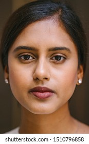 Close up portrait head shot of a young, intelligent-looking, confident and beautiful Indian Asian woman in a casual white blouse. She has a neutral expression as she looks at the camera.