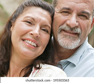 Close up portrait of a healthy and attractive senior couple relaxing on holiday, leaning on each other and being loving and close. Mature people enjoying romance and retirement, outdoors lifestyle.