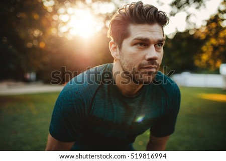 Close up portrait of healthy young man standing outdoors in park and looking away. Confident young man ready of workout.