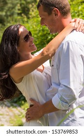 Close up portrait of hugging couple outdoors sunny park