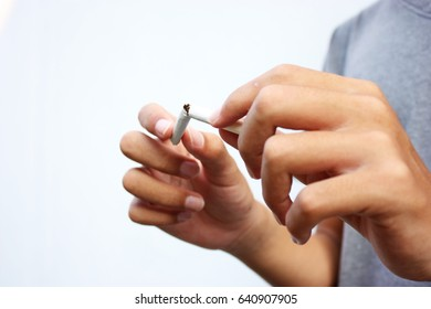 Close up portrait of human hands breaking down cigarette to pieces. Studio shot selective focus isolated on white background. Quit smoking addiction concept. Stop smoking message