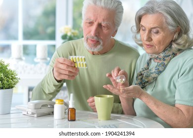 Close up portrait of ill senior beautiful couple with pills posing at home