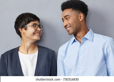 Close up portrait of interracial business couple dressed formally, look with happy expressions at each other, rejoice successful signed contract, have triumph. Mixed race relationship, career concept