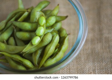 close up portrait of Japanese food edamame nibbles, boiled green soybeans