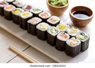 close up portrait of japanese food mini maki sushi platter on white wooden table served with wasabi and soy sauce