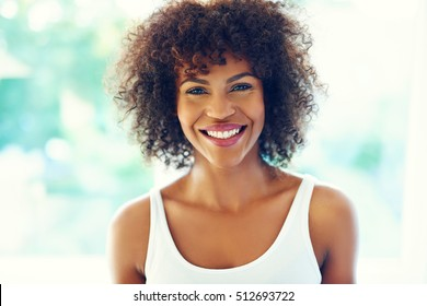 Close up portrait of joyful beautiful African-American woman looking at camera and smiling.