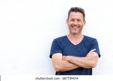 Close up portrait of laughing casual man standing with arms crossed