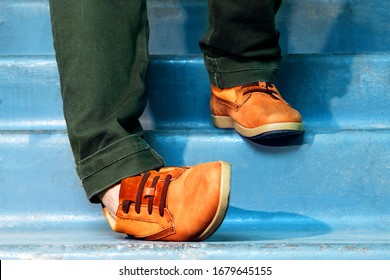 Close up portrait of legs with sneakers walking down stairs and spraining or dislocating ankle.