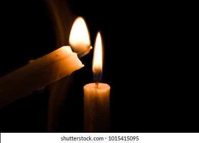 close up portrait of lights up the candles with another burning candle on black background