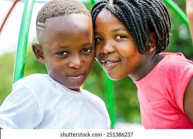 Close up portrait of little African brother and sister joining heads outdoors in park.