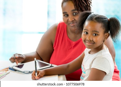 Close up portrait of little african girl doing school work. Mother helping and supervising kid at home.