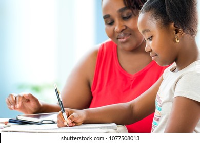 Close up portrait of little african girl doing home work. Teacher giving private after school lessons with digital tablet at home.
