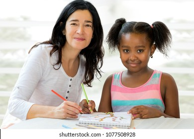 Close up portrait of little african girl and caucasian teacher at home. Kid having private art drawing after school lesson.