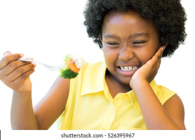 Close up portrait of little african girl refusing to eat fork with vegetables.Child pulling up nose Isolated on white background.