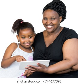 Close up portrait of little african girl and mother holding digital tablet isolated on white background.Mother and daughter looking at camera.