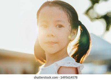 Close up portrait of little asian girl with dimples in park during sunset