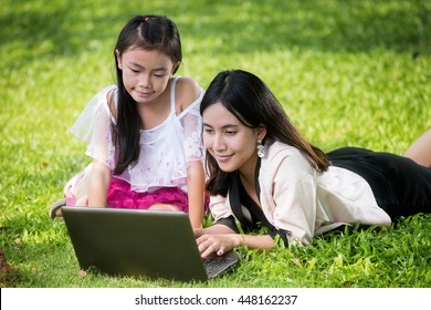 Close up portrait of little asian girl with braids and mother with laptop. Kid typing on laptop against green background outdoors.