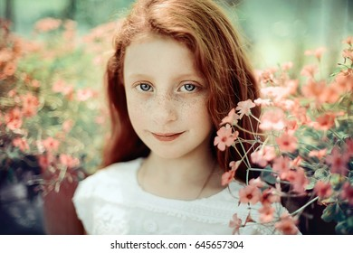 Close portrait of a little beautiful girl with red hair and blue eyes. The girl is surrounded by small flowers in Botanic Garden in Tirana.