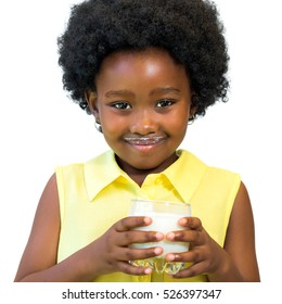 Close up portrait of little black girl holding glass of milk.Kid with afro hairstyle Isolated on white background.