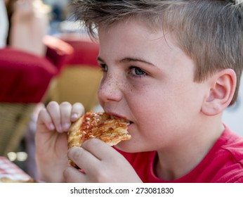 close up portrait of a little boy eating a pizza slice