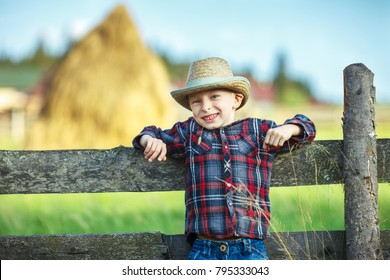 Close up portrait of little boy in hat with straw in mouth leaned on wooden fence. Happy chilhood concept. Vacation