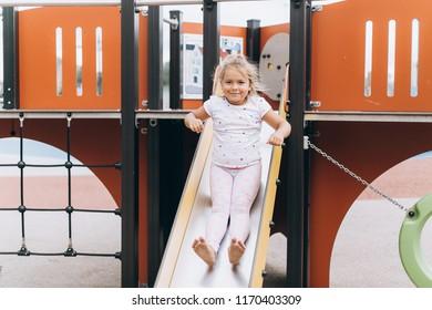 Close up portrait of little cute cheerful caucasian girl having fun in children playground