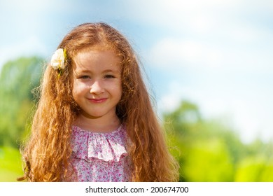 Close portrait of little girl with long curly hair in the park