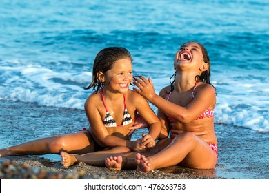 Close up portrait of little girls laughing together.Two kids sitting on sand with waves in background.