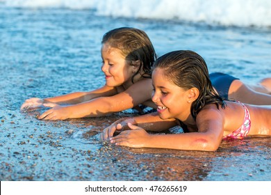 Close up portrait of little girls looking for shells on beach.