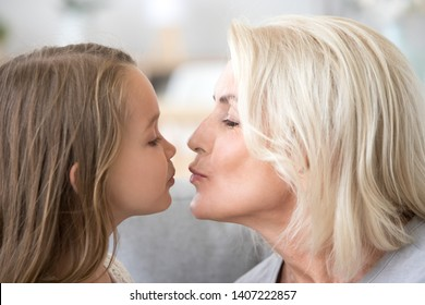 Close up portrait of little preschool granddaughter kissing loving attractive grandmother. Friendly relationships best friends two generations middle aged female and small kid relative people concept