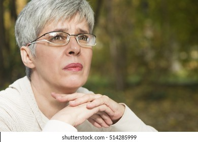 Close up portrait of lovely middle aged woman in the autumn park