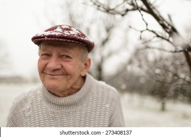 Close up portrait of lovely smiling grandpa. Grandfather in snowy outdoors.