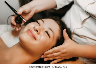 Close up portrait of a lovely woman leaning on a spa bed with closed eyes smiling while having oxygenotheraphy on her face in a wellness center.