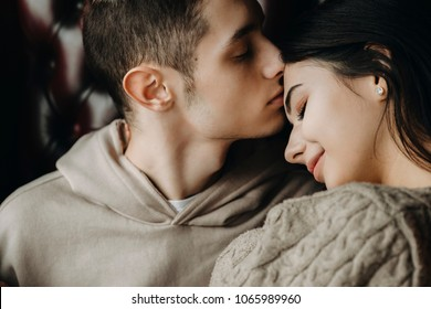Close up portrait of a lovely young couple sitting on a leather chair while boy is kissing his girlfriend on forehead.