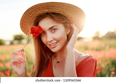 Close up portrait of lovely young romantic woman with poppy flower in hand posing on field background. Wearing straw hat. Soft colors.