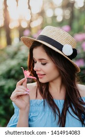 Close up portrait of lovely young romantic woman with flower in hand posing on sunset. Wearing straw hat.
