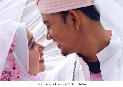 close up portrait of a malay bride and groom under veil with lovely emotion. Concept of malay wedding and marriage