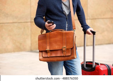 Close up portrait of male traveler standing outdoors with cellphone and travel bag