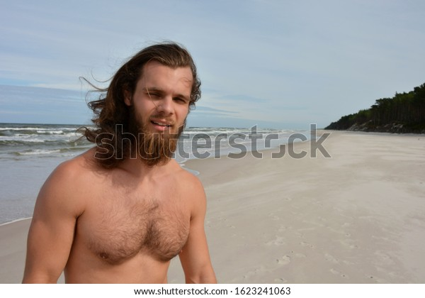 Close up portrait of man with beard, smiling, outdoor, with sea in background.