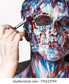 close up portrait of man with colorful face painting. emotional beautiful guy. face painting in process