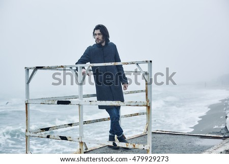 f5b9548595e Close up portrait of Man in a gray coat standing on a pier.sea in