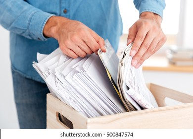 Close up portrait of man hands looking for documents in stack of folders on the office table