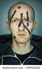 Close up portrait of man hiding his face from camera recognition with special camouflage makeup. Digital privacy in big city concept image.