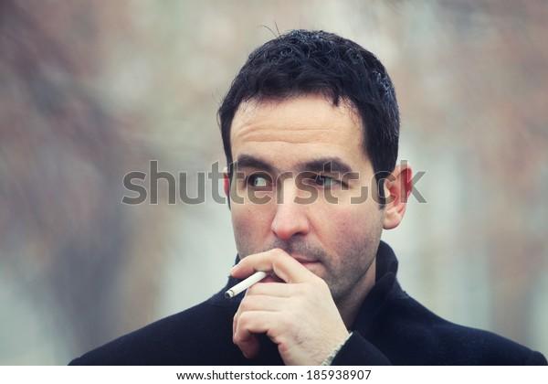 Close up portrait of a man smoking cigarette