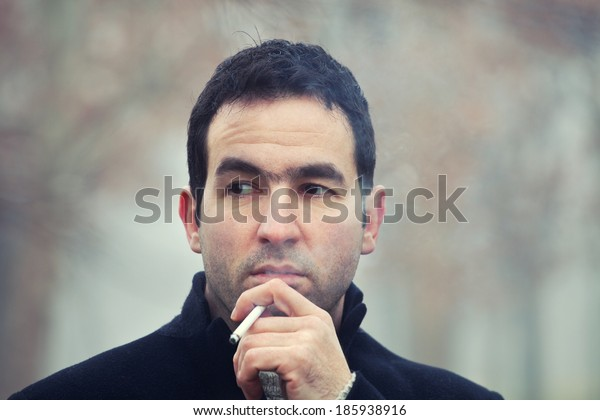 Close up portrait of a man smoking cigarette