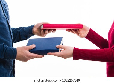Close up portrait of man and women students exchanging different books isolated on white. Literature sharing between people. Give a friend to read as present. Person borrow textbook, swap of knowledge