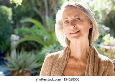 Close up portrait of a mature attractive woman sitting and relaxing in a home garden during a bright and golden summer sunny day, smiling outdoors.