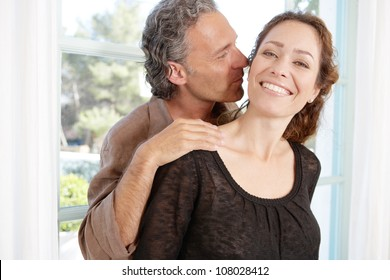 Close up portrait of a mature couple being playful and kissing at home